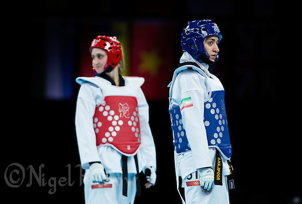 10 AUG 2012 - LONDON, GBR - Sousan Hajipourgoli (IRI) (right) of Iran and  Carmen Marton (AUS) (left) of Australia wait for the referees decision after an appeal during their women's -67kg category preliminary round contest at the London 2012 Olympic Games Taekwondo at Excel in London, Great Britain .(PHOTO (C) 2012 NIGEL FARROW) (NIGEL FARROW/(C) 2012 NIGEL FARROW)