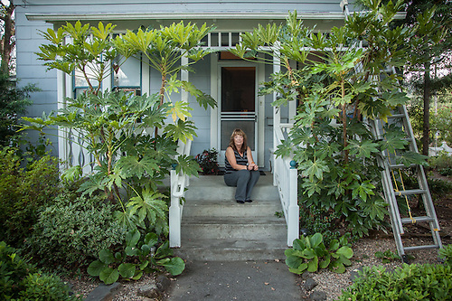 "Nanci M. Smith on her porch of her home on Cedar Street in Calistoga.  ""A branch from one of my 300 year old trees fell in July and took out the corner of my porch...I went into the house for a drink of water and it saved my life."" (Clark James Mishler)"