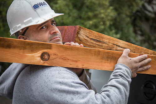 Construction crew member and Oakland resident Mike Diaz unloads timber at the site of the new Calistoga Teen Center at the corders of Grant and Stevenson Streets (© 2017 Clark James Mishler)