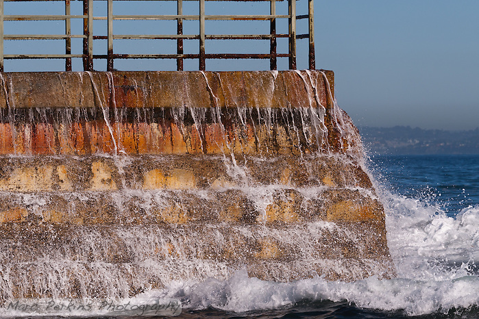 Water cascades over a brick sea wall at La Jolla Children's Pool on a gorgeous sunny winter day.  A wave has just hit the wall, and white foamy drops  are dripping and streaming off the bricks, as the water foams to the side and front of the wall.  The water and sky, though, are perfectly calm, making a great contrast. (Marc C. Perkins)