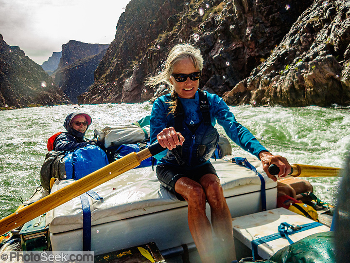 AZRA Trip leader Lorna Corson rows a rapid on Day 6 of 16 days rafting 226 miles down the Colorado River in Grand Canyon National Park, Arizona, USA. For this photo's licensing options, please inquire at PhotoSeek.com. (© Tom Dempsey / PhotoSeek.com)