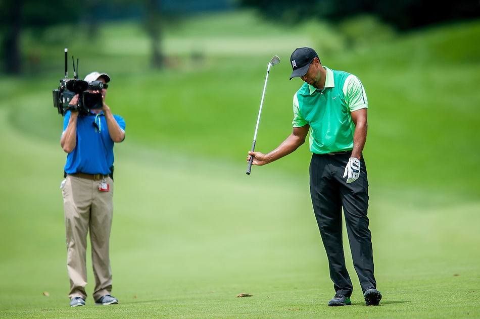 Tiger Woods reacts to his approach shot to the 9th hole during the first round of the Quicken Loans National golf tournament on Wednesday at Congressional Country Club in Bethesda, Maryland.  This marked  Woods' return to competition for the first time in three months after having surgery just a week before the Masters in April of this year. (Pete Marovich/Corbis)