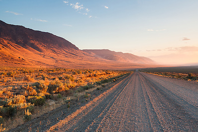 The long gravel Fields-Denio road in Southeast Oregon parallels the Steens range and vanishes off into a curve in the distance seen right after sunrise. (Benjamin Chase)