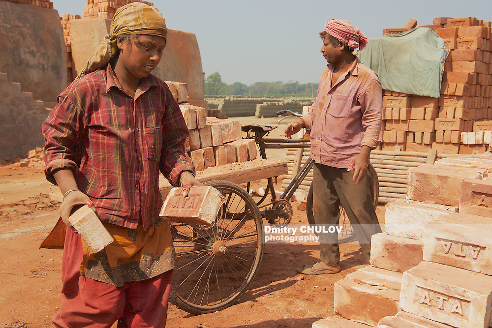 DHAKA, BANGLADESH - FEBRUARY 19, 2014: Two unidentified workers move bricks at a factory in Dhaka, Bangladesh. In Bangladesh women often attend very hard jobs. (Dmitry Chulov)