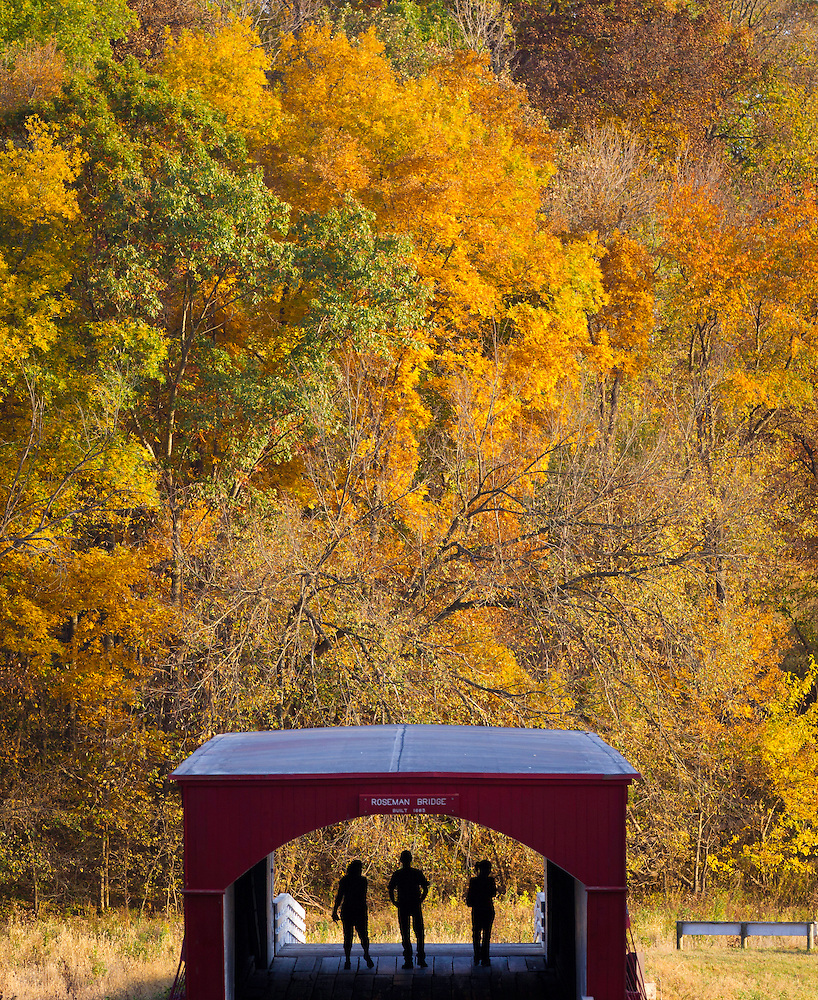 A trio of visitors stroll Roseman Bridge, one of Madison County's six remaining historic covered bridges as Fall colors bloom west of Winterset, Iowa on October 9. (Christopher Gannon)