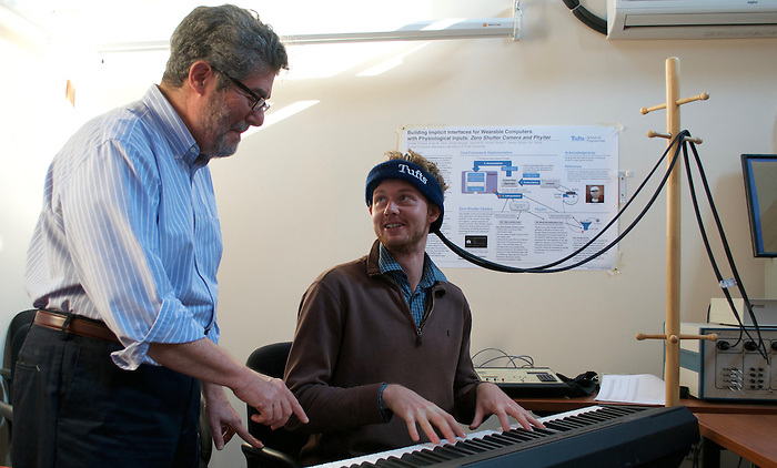 BACh mock experiment at Tufts HCI Lab. PhD student places electrodes on his head (holds them with band) in order to assess electrical impulses while playing simple assigned melodies on the keyboard. Professor Jacob explains the melody to him. 3/8/16-Medford/Somerville, MA- BACh experiment @ Tufts HCI Lab. Professor Robert Jacob mentors PhD students in the pictures. on March 08th, 2016. (Maria Ferraz / The Tufts Daily) (Daily Photo)