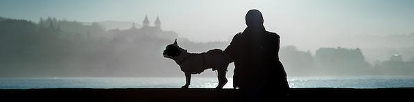Silhouette of man and his dog sat on balaustrade in San Sebastian (Spain) (Carlos Peñalba)