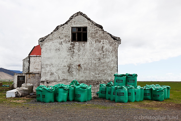 Old farm house in South Iceland. Large green sacks of fertilizer in front of the building. (Christopher Lund/©2011 Christopher Lund)