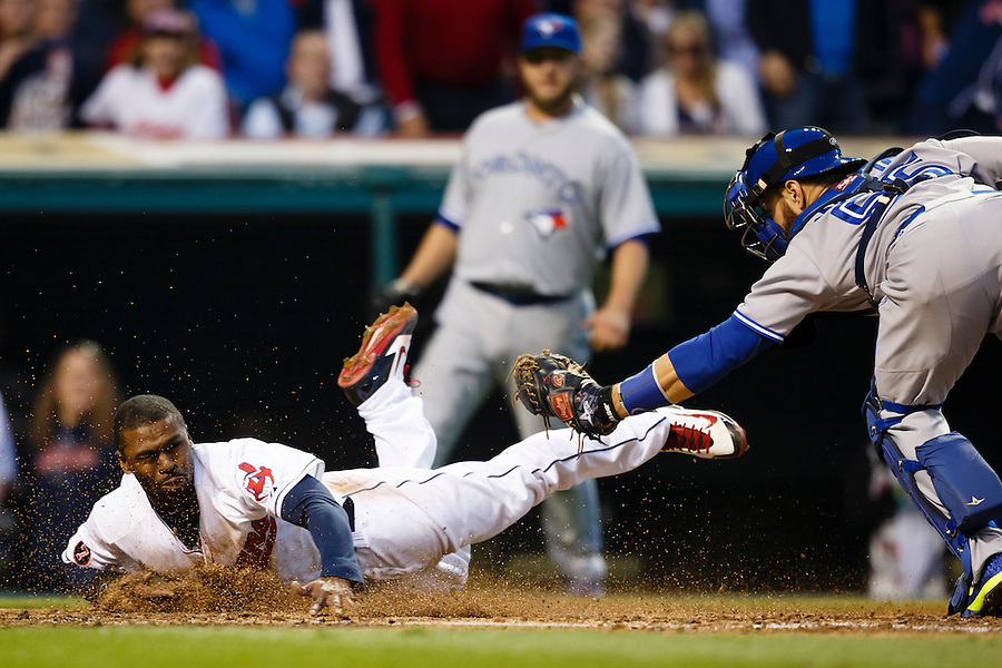 May 1, 2015; Cleveland, OH, USA; Cleveland Indians center fielder Michael Bourn (24) dives into home and is tagged out by Toronto Blue Jays catcher Russell Martin (55) in the fourth inning at Progressive Field. Bourn was called safe on the field but the call was overturned on replay challenge. Mandatory Credit: Rick Osentoski-USA TODAY Sports (Rick Osentoski/Rick Osentoski-USA TODAY Sports)