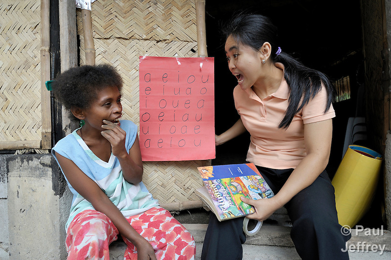 United Methodist Pastor Leslie Dela Cruz, right, teaches basic literacy, including making vowel sounds, to Janet Tamtan, an Aetna indigenous woman in the Philippine village of Camachile, where the United Methodist Church has a pastoral presence among Aetnas who were displaced by the eruption of Mt Pinatubo. (Paul Jeffrey)