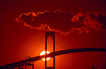 USA, Newport, RI - Setting sun centered behind tower of Newport Bridge with red filter. (Alexander Nesbitt)