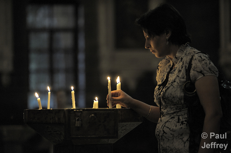 A worshipper lights candles in St. Paul's Melkite Greek Catholic Church in Damascus, Syria. (Paul Jeffrey)