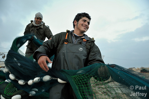 Fishermen pull in a net at the dock in Gaza City. Under the 1993 Oslo Peace Accords, the people of the Gaza Strip were allowed to fish out to 20 nautical miles from their coastline, yet since the Israeli military imposed a naval blockade in 2007 they have been limited to just three nautical miles. In practice, fishers who venture beyond two nautical miles are shot at by Israeli gunboats; several have been injured and some killed. Despite having 40 kilometers of coastline and a long tradition as fishers, many fishers are unemployed and the people of Gaza are forced to import fish from Israel. And what fishing they can do close to shore mostly involves the harvest of immature fish, which biologists warn has a negative impact on fish stocks in the region....