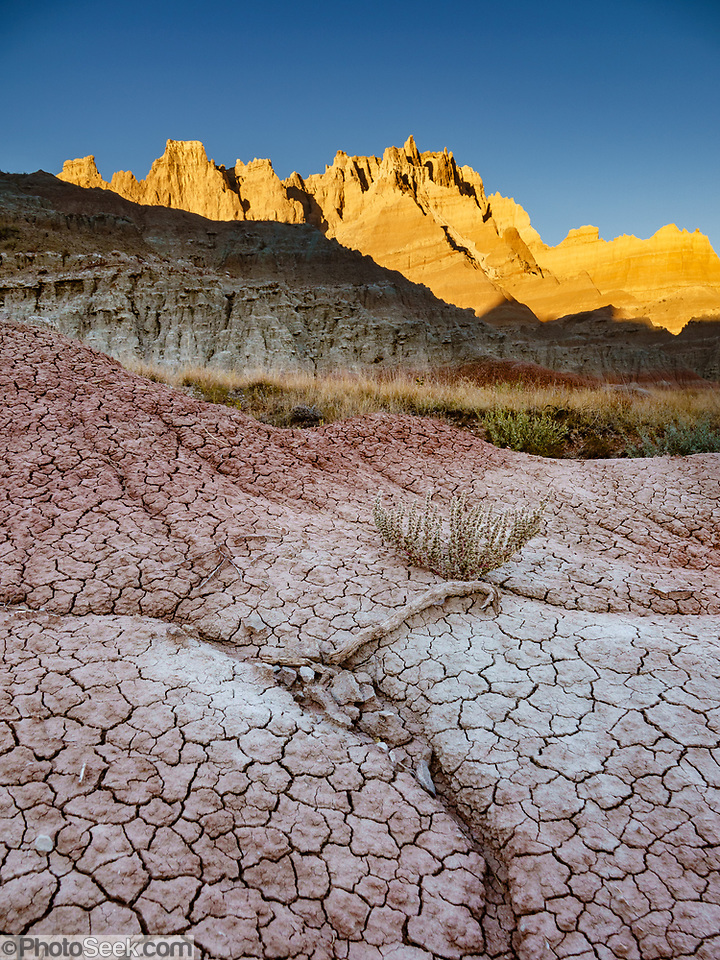 Sunset illuminates the Badlands Wall above cracked mud near Ben Reifel Visitor Center in Badlands National Park, South Dakota, USA. The intricately carved cliff of the Badlands Wall constantly retreats as it erodes and washes into the White River Valley below. (© Tom Dempsey / PhotoSeek.com)