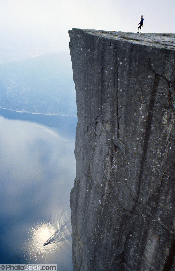 A solo hiker walks atop the Pulpit Rock (Prekestolen) 1959 feet above a car ferry on Lysefjord, Forsand municipality, Rogaland county, Ryfylke traditional district, Norway, Europe. (© Tom Dempsey / PhotoSeek.com)