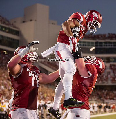 Sep 20, 2014; Fayetteville, AR, USA; Arkansas Razorbacks offensive tackle Frank Ragnow (72) lifts wide receiver Jared Cornelius (1) as offensive tackle Dan Skipper (76) looks on after Cornelius scored a touchdown during the first half of a game against the Northern Illinois University Huskies at Donald W. Reynolds Razorback Stadium. Mandatory Credit: Beth Hall-USA TODAY Sports (Beth Hall/Beth Hall-USA TODAY Sports)