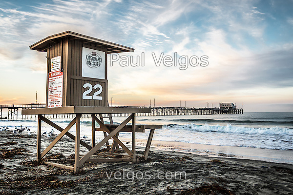 Photo of Newport Beach lifeguard tower 22 and Newport Pier at sunrise. Newport Pier is located on Balboa Peninsula in Orange County Southern California along the Pacific Ocean. Photo is high resolution HDR style. (Photographer: Paul Velgos)