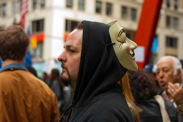 Protester wearing a Guy Fawkes mask looks on at an interview in progress in Zuccotti Park. October 21, 2011. (Emon Hassan)