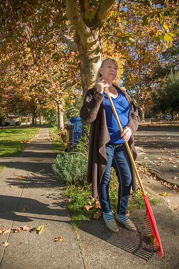 "Russian imigrant Liubov Hattaway rakes leaves in front of her home in Calistoga.  ""I want make all people friendly...like the people of Calistoga."" (Clark James Mishler)"