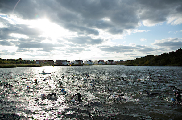 16 AUG 2014 - DARTFORD, GBR - Competitors head for the next buoy as they swim their first lap of the 2014 Midnight Wo/Man triathlon in The Bridge Lakes in Dartford, Great Britain (PHOTO COPYRIGHT © 2014 NIGEL FARROW, ALL RIGHTS RESERVED) (NIGEL FARROW/COPYRIGHT © 2014 NIGEL FARROW : www.nigelfarrow.com)