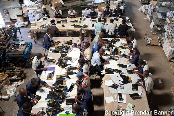 Workers at Colourprint in Nairobi assemble brochures for Barclays Bank. (Photographer: Brendan Bannon)