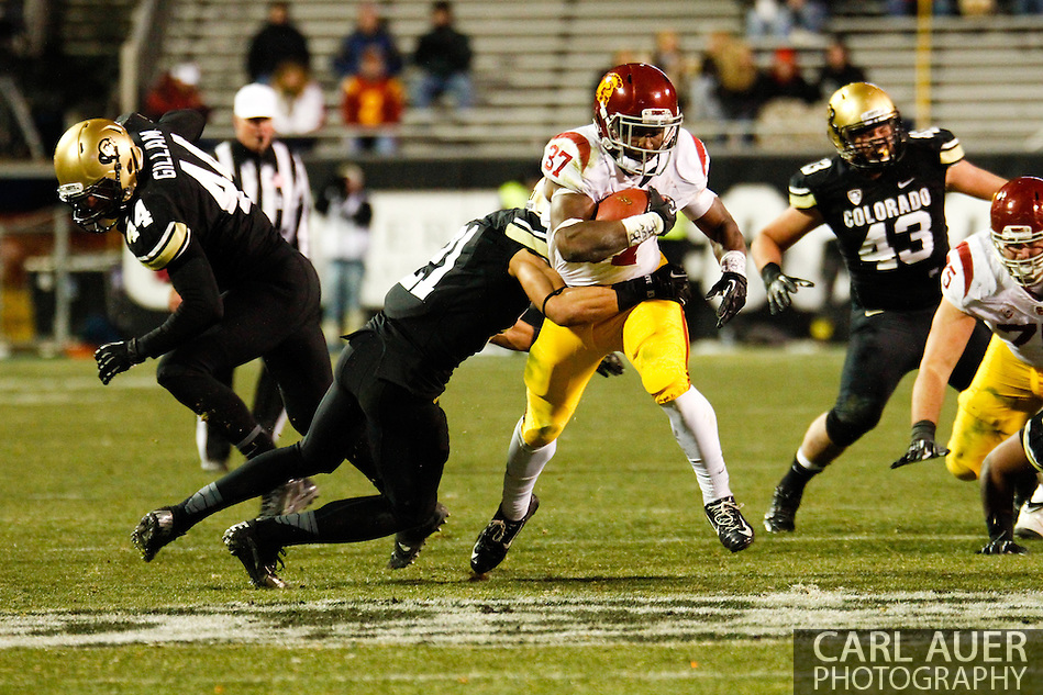 November 23rd, 2013: USC Trojans sophomore running back Javorius Allen (37) tries to break a tackle by Colorado Buffaloes junior defensive back Jered Bell (21) in the third quarter of the NCAA Football game between the University of Southern California Trojans and the University of Colorado Buffaloes at Folsom Field in Boulder, Colorado (Carl Auer/ZUMAPRESS.com)