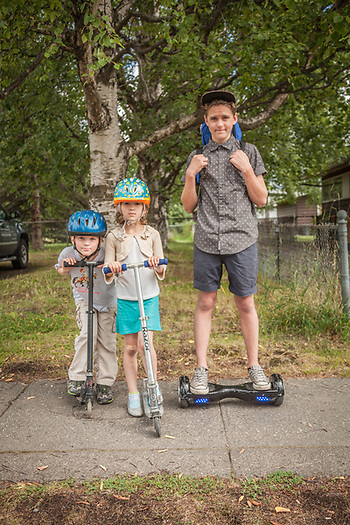 Seven year old Jake and Gracey with their fourteen year old brother, Ben Breun, on his Smart Balance Wheel in Anchorage's South Addition neighborhood. (© Clark James Mishler)