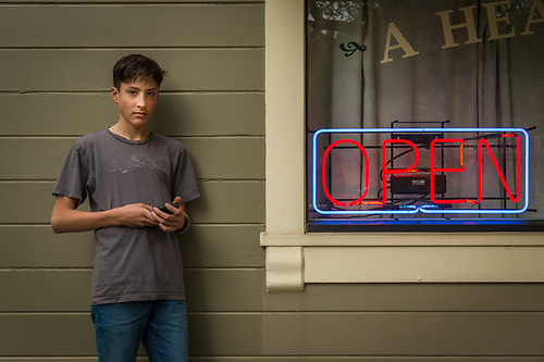 Fifteen year old Emmet Bowen waits for his ride home after a haircut in downtown Calistoga. (Clark James Mishler)