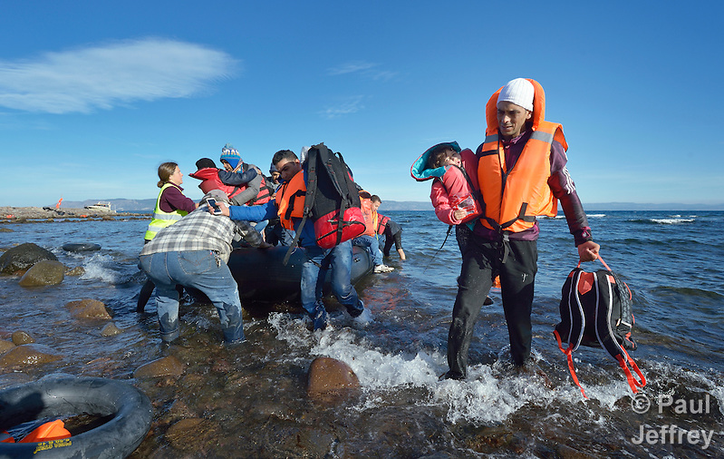 Refugees land on a beach near Molyvos, on the Greek island of Lesbos, on November 3, 2015, after crossing the Aegean Sea from Turkey. Local and international volunteers welcomed the arriving refugees with food and medical care and dry clothes before the newcomers proceeded on their way toward western Europe. Their boat to Greece was provided by Turkish traffickers to whom the refugees paid huge sums to arrive in Greece. (Paul Jeffrey)