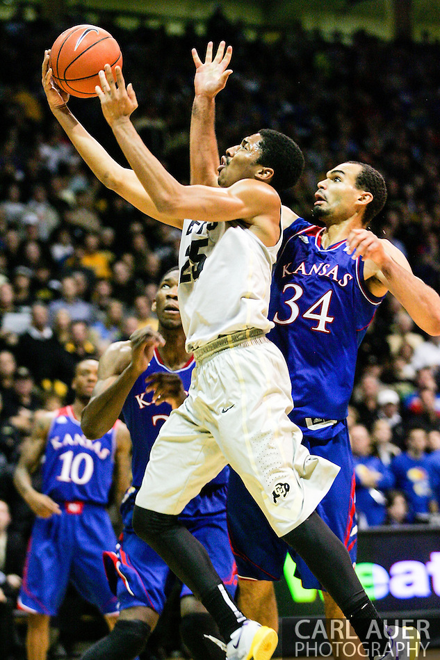 December 7th, 2013:  Colorado Buffaloes junior guard Spencer Dinwiddie (25) glides to the basket past Kansas Jayhawks sophomore forward Perry Ellis (34) in the second half of the NCAA Basketball game between the Kansas Jayhawks and the University of Colorado Buffaloes at the Coors Events Center in Boulder, Colorado (Carl Auer/ZUMAPRESS.com)