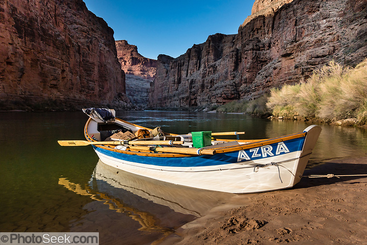 """Arizona Raft Adventures (AZRA) dory boat at Tatahatso Wash Camp (Mile 37.9) on the Colorado River in Marble Canyon in Grand Canyon National Park, Arizona, USA. Marble Canyon runs from Lees Ferry at River Mile 0 to the confluence with the Little Colorado River at Mile 62, which marks the beginning of the Grand Canyon. Although John Wesley Powell knew that no marble was found here when he named Marble Canyon, he thought the polished limestone looked like marble. In his words, """"The limestone of the canyon is often polished, and makes a beautiful marble. Sometimes the rocks are of many colors – white, gray, pink, and purple, with saffron tints."""" For this photo's licensing options, please inquire at PhotoSeek.com. . (© Tom Dempsey / PhotoSeek.com)"""