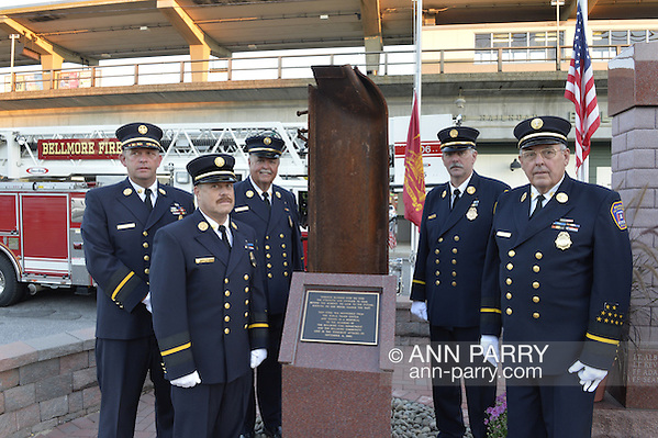 Bellmore, New York, USA. September 11, 2015. L-R, Bellmore Fire Dept. Chief DANIEL HOLL, Pastor and Chaplain JAMES BARNUM, 1st Deputy VINCENT MONTERA, 2nd Deputy TOM STOERGEN, and Chaplain DENNIS RICH stand next to a monument that's a piece of structural steel from the Twin Towers, during the Bellmore Memorial Ceremony for 3 Bellmore volunteer firefighters and 7 residents who died due to 9/11 NYC terrorist attacks. Elevated platform of Bellmore LIRR Station is in background. (Ann Parry/Ann Parry, ann-parry.com)