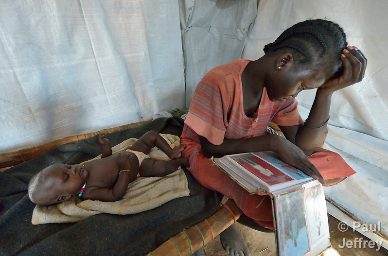 Nyanthem Mayol stares at photos of her relatives while her baby daughter Sara sleeps at her side in a temporary shelter near Ajuong Thok, South Sudan, to where they fled after fighting broke out in their home town of Bentieu in late 2013. The mother and daughter arrived here in March 2014, after weeks of walking through the bush. Displaced families here are living with their relatives on the edge of a camp filled with thousands of refugees from Sudan's Nuba Mountains. (Paul Jeffrey)