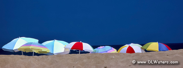 Beach umbrellas lined up on a summer beach day in Kitty Hawk North Carolina. (Daniel Waters)