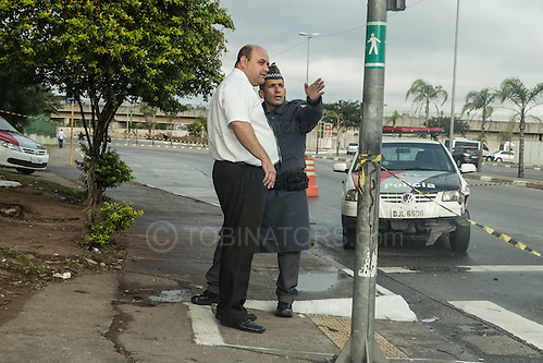 My taxi driver (left) asks directions to the stadium in Sao Paulo from a policeman (right) of a crashed police car (background), despite the stadium being in plain sight and really rather massive just behind me.  Photo by Andrew Tobin/Tobinators Ltd (Andrew Tobin/Tobinators)