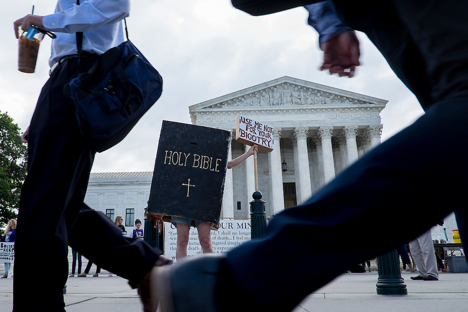 Activists on both sides of the contraceptive debate wait outside of the Supreme Court  in Washington, District of Columbia, U.S., on Monday, June 30, 2014 as the Court prepares to hand down its ruling on whether Obamacare can mandate contraception coverage specifically for certain businesses that object for religious reasons. (Pete Marovich/Bloomberg)