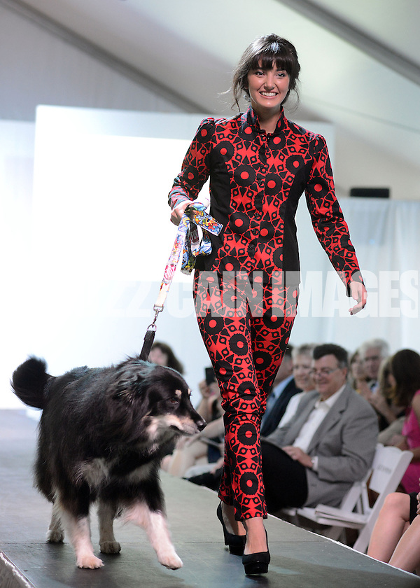 DOYLESTOWN, PA - JUNE 06: A model walks the runway with Lucy the dog during the Canines on the Catwalk fashion show June 6, 2014 at the Michener Museum in Doylestown, Pennsylvania. Canines on the Catwalk is a fashion show coupling professional models, high-end clothes and dogs. The program benefits animal rescue  (Photo by William Thomas Cain/Cain Images) (William Thomas Cain)