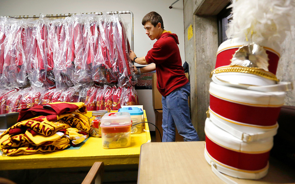 Jonny Schmidt, a freshman clarinetist in the Iowa State marching band, carts some of the 350 freshly-dry cleaned marching band uniforms into a Music Hall storage room on Monday, March 30, 2015. The uniforms will be assigned to student musicians once the marching band is finalized in August. (photo by Christopher Gannon) (Christopher Gannon)