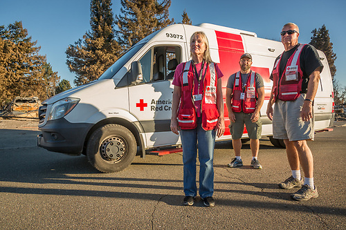 Red Cross Volunteers Doris Davis (TX), Rick Crump (MO) and Ron Scott (AZ), hand out supplies to those whose homes were lost to the Tubbs Fire in the Mark West Estates in Santa Rosa. (Clark James Mishler)