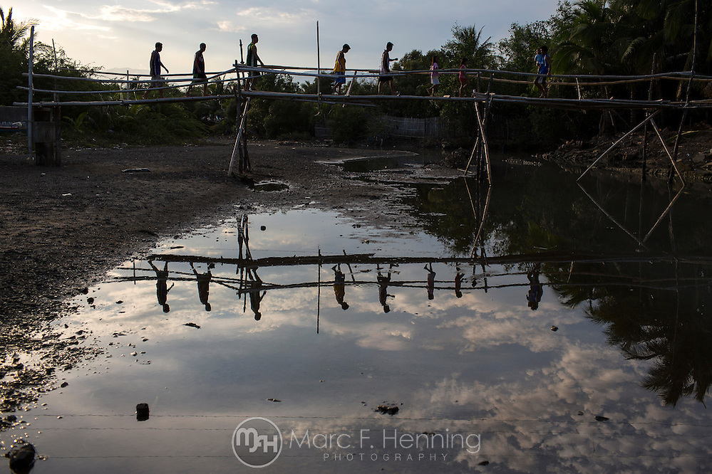Photo by Marc F. Henning Mansalenos cross a bamboo footbridge over the Nalwak River in the evening April 28, 2014, on their way towards the center of town in Mansalay, Oriental Mindoro, Philippines. The bamboo bridge is being replaced with a permanent cable hanging bridge, which is currently under construction. (MARC F. HENNING/MARC F. HENNING PHOTOGRAPHY)