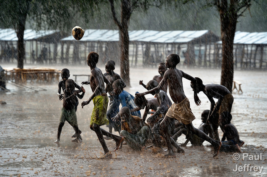 Children play football during a rainstorm in the Doro refugee camp in South Sudan's Upper Nile State. More than 110,000 refugees were living in four camps in Maban County in October 2012, but officials expected more would arrive once the rainy season ended and people could cross rivers that block the routes from Sudan's Blue Nile area, where Sudanese military has been bombing civilian populations as part of its response to a local insurgency. Conditions in the camps are often grim, with outbreaks of diseases such as Hepatitis E.