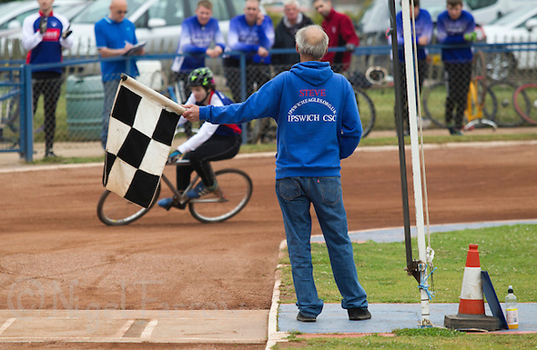 "14 JUN 2015 - IPSWICH, GBR - Ipswich Eagles flag man Steve Rumbold holds out the chequered flag at the end of a heat during the Elite League cycle speedway fixture between Ipswich Eagles and Poole Comets at Whitton Sports and Community Centre in Ipswich, Suffolk, Great Britain. Father of elite team rider Charlie Rumbold, Steve was once removed from his flag man duties during a match when he ""questioned"" an opposition riders actions (PHOTO COPYRIGHT © 2015 NIGEL FARROW, ALL RIGHTS RESERVED) (NIGEL FARROW/COPYRIGHT © 2015 NIGEL FARROW : www.nigelfarrow.com)"