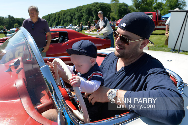 Old Westbury, New York, United States. 7th June 2015. JACKSON STERN, five-months-old, holds the steering wheel of a red 1954 Chevrolet Corvette convertible as he sits in the lap of his father JOSHUA STERN, at the 50th Annual Spring Meet Car Show sponsored by Greater New York Region Antique Automobile Club of America. The Corvette, which was parked, is owned by Adam Heller of NYC. Over 1,000 antique, classic, and custom cars participated at the popular Long Island vintage car show held at historic Old Westbury Gardens. (Ann Parry/Ann Parry, ann-parry.com)