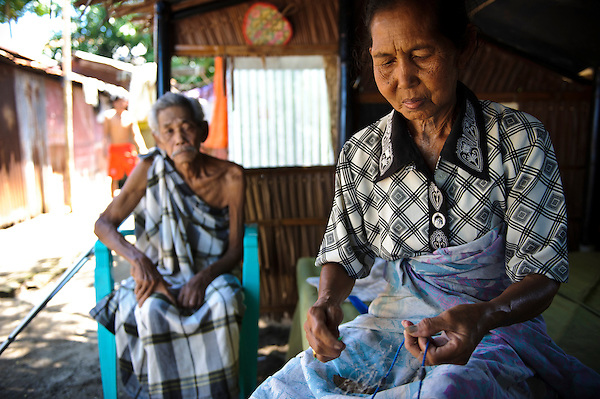 An elderly woman repairing fishing nets whilst being watched by her husband, Lae Lae, Makassar, Sulawesi, Indonesia. (Matthew Oldfield)