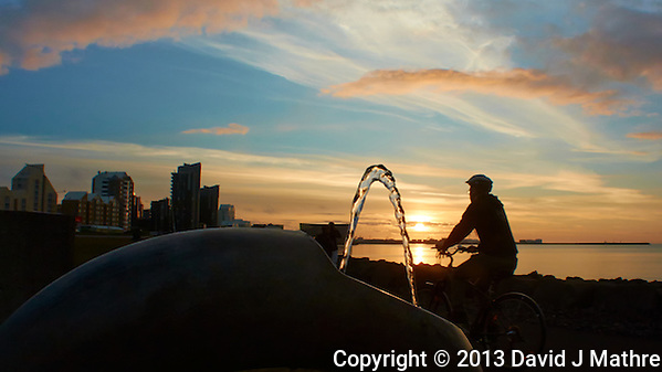 Sunset Along the Reykjavik Harbor Walkway. Image taken with a Nikon 1 V2 camera and 10 mm f/2.8 lens (ISO 160, 10 mm, f/8, 1/400 sec). The foreground is a water fountain, and the bicycle rider just happened to go by as I took the image. (David J Mathre)