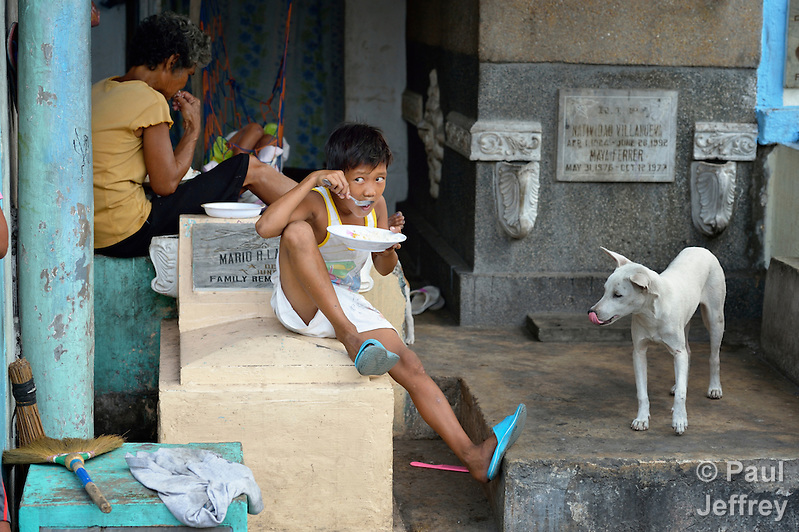 "In the capital of the Philippines, a mother and her son eat in a mausoleum that is their home in the Manila North Cemetery. Hundreds of poor families live here, dwelling in and between the tombs and mausoleums of the city's wealthy. They are often discriminated against, and many of their children don't go to school because they're too hungry to study and they're often called ""vampires"" by their classmates. With support from United Methodist Women, KKFI provides classroom education and meals to kids from the cemetery at a nearby United Methodist Church. (Paul Jeffrey)"