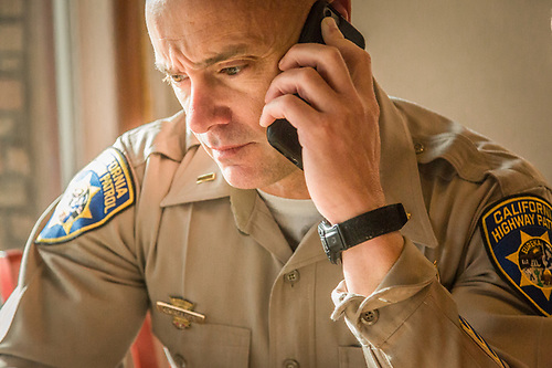 "California Highway Patrol Lieutenant Ken Roberts stays in touch with his office during a ""Coffee with a Cop"" event at Bella's Bakery in Calistoga. (Clark James Mishler)"