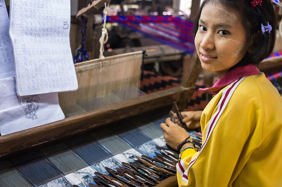 MANDALAY, MYANMAR - CIRCA DECEMBER 2013: Young woman working webing typical Burmese fabrics in Amarpura in Myanmar (Daniel Korzeniewski)
