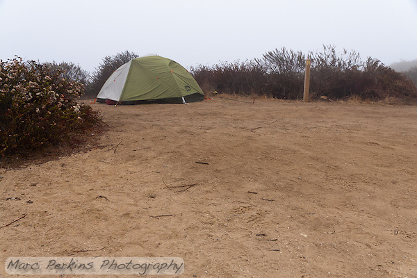 My REI Quarterdome T2 tent set up with rainfly at Crystal Cove State Park's Lower Moro campground.  Space markers numbering each camping spot are scattered around the campground. (Marc C. Perkins)