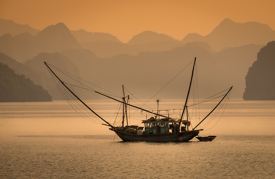 HA LONG BAY, VIETNAM - CIRCA SEPTEMBER 2014:  Fishing boat in Halong Bay, Vietnam at sunset. (Daniel Korzeniewski)